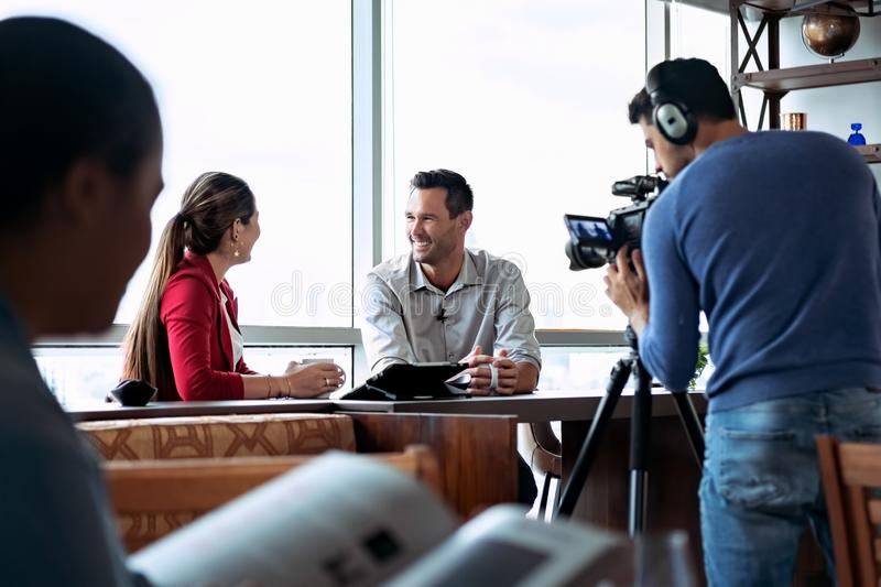 Business Man In Office Talking And Smiling During Corporate Interview. Happy businessman during corporate interview with female journalist. Manager answering stock image