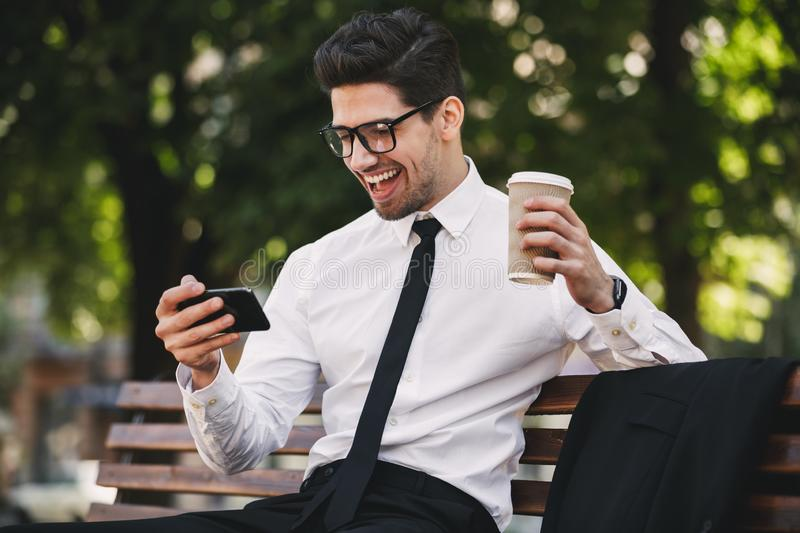 Business man outdoors in the park play games by phone drinking coffee. stock image