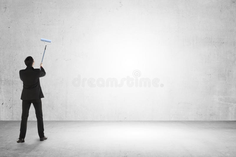 Business man paint something on empty wall stock photo