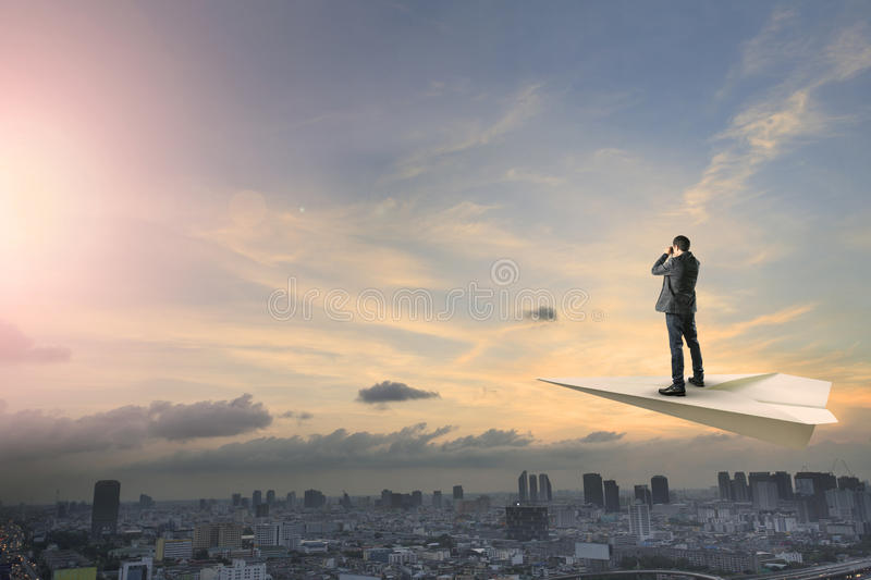 Business man on paper plane flying above urban scene spying shot stock image