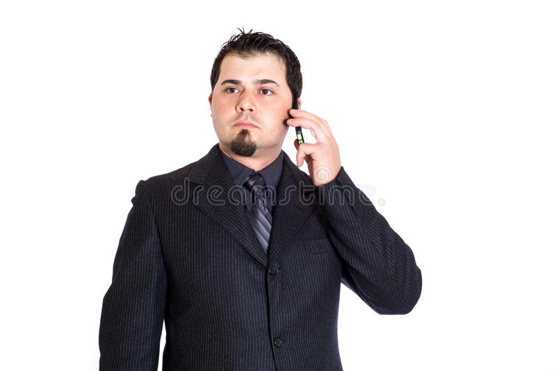 Business man on phone distracted. A distracted looking businessman on the phone. White background royalty free stock photos