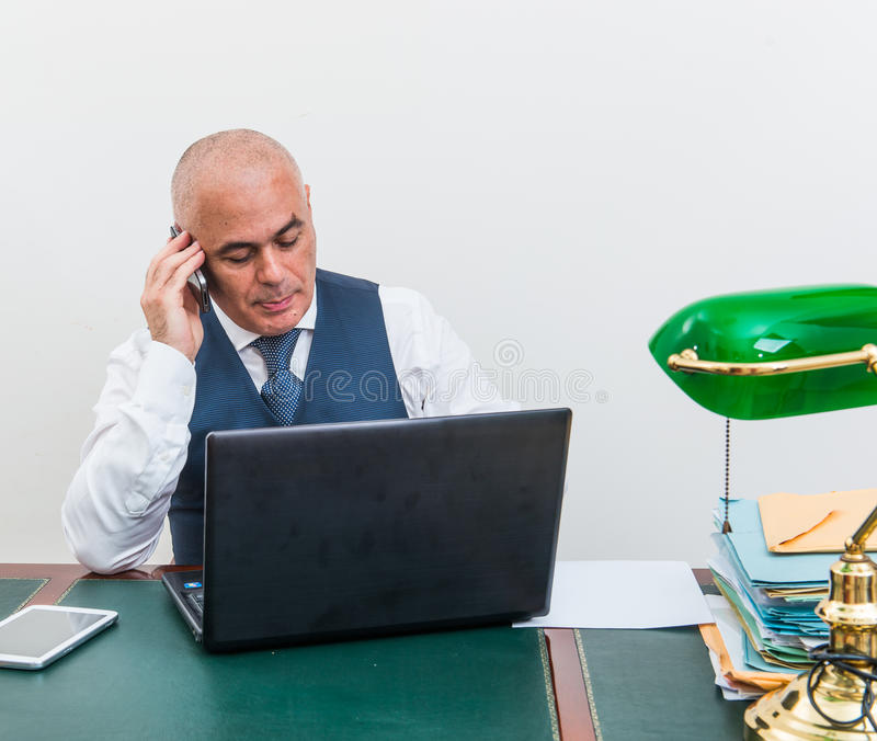 A business man on the phone and pc, at desk, in conference call royalty free stock photo