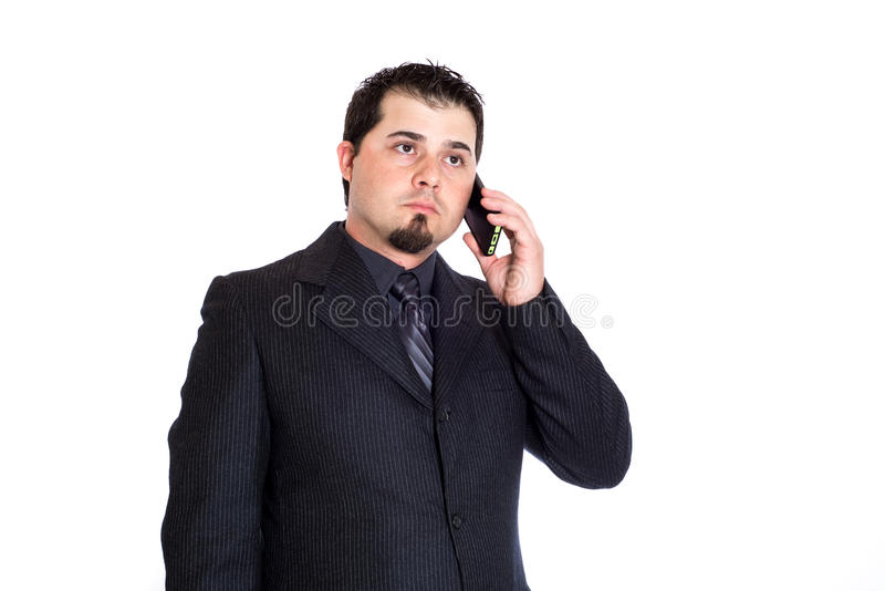 Business man on phone serious. A serious looking businessman on the phone. White background stock image