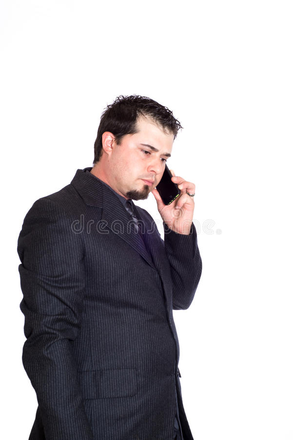 Business man on phone serious. A serious looking businessman on the phone. White background royalty free stock photos