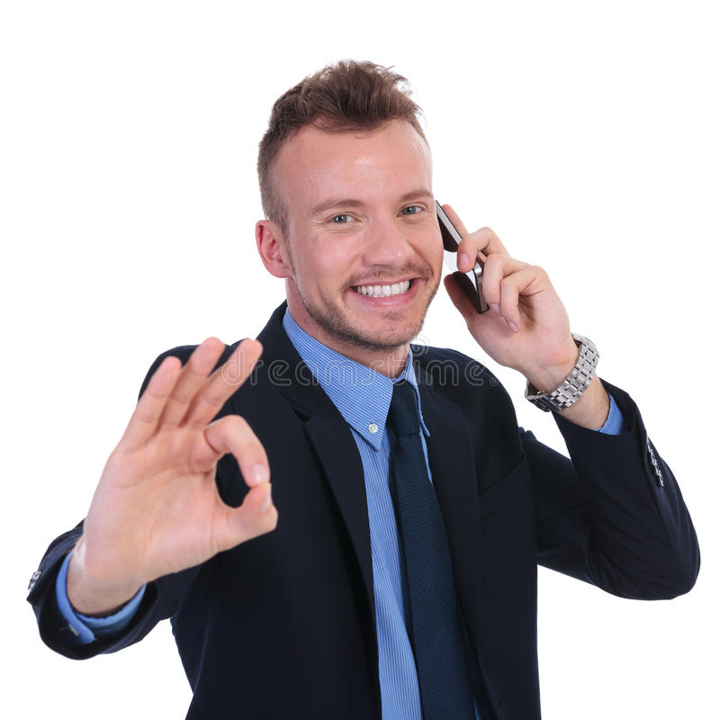 Business man on the phone shows ok. Young business man talking on the phone and showing the ok gesture. on white background royalty free stock photography