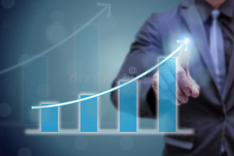 Business man point hand on the top of arrow graph with high rate of growth. The success and growing growth graph in the company or. Industrial after investment royalty free stock photo