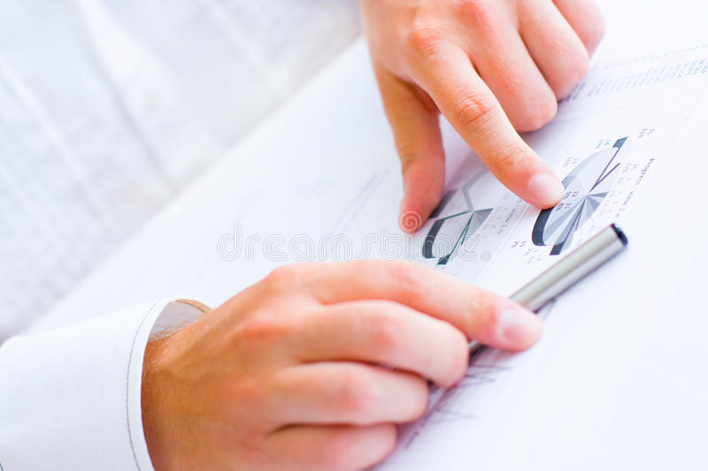 Business man pointing to charts and graphs royalty free stock images