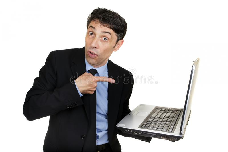 Business man pointing to his laptop. Business man pointing to his open laptop that he is carrying in his hand with a surprised guilty expression isolated on stock photos