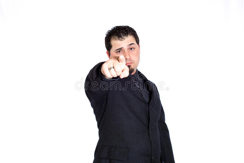 Business man pointing at you. A businessman pointing at you with a raised eyebrow. White background royalty free stock images