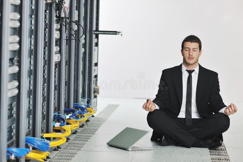 Business man practice yoga at network server room. Young handsome business man in black suit and tie practice yoga and relax at network server room while