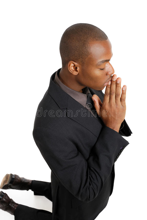Business man praying on his knees. This is an image of business man on his knees praying royalty free stock photography