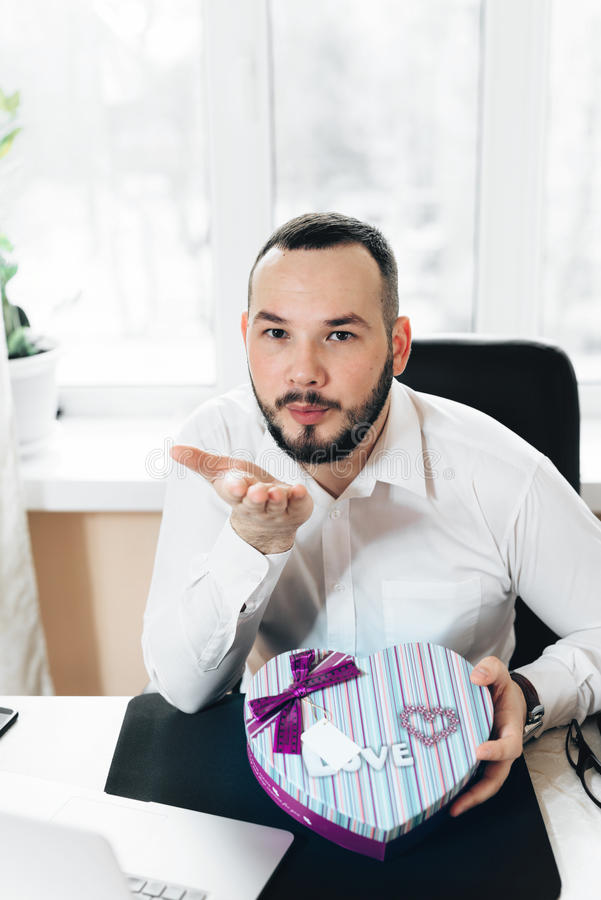 Business man prepared a gift in the form of heart stock photo