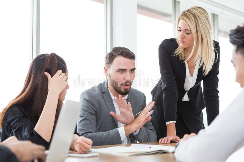 business man presenting and disagree sign  in meeting room . Group of young business people brainstorming together in office. stock photography