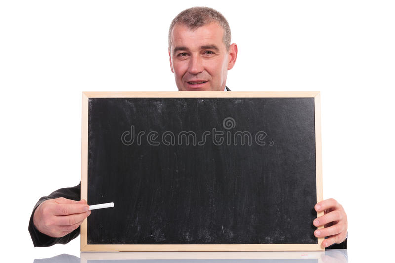 Business man presents with chalk on small blackboard. Business man pointing with a piece of chalk at the small blackboard he is holding, while looking into the royalty free stock images