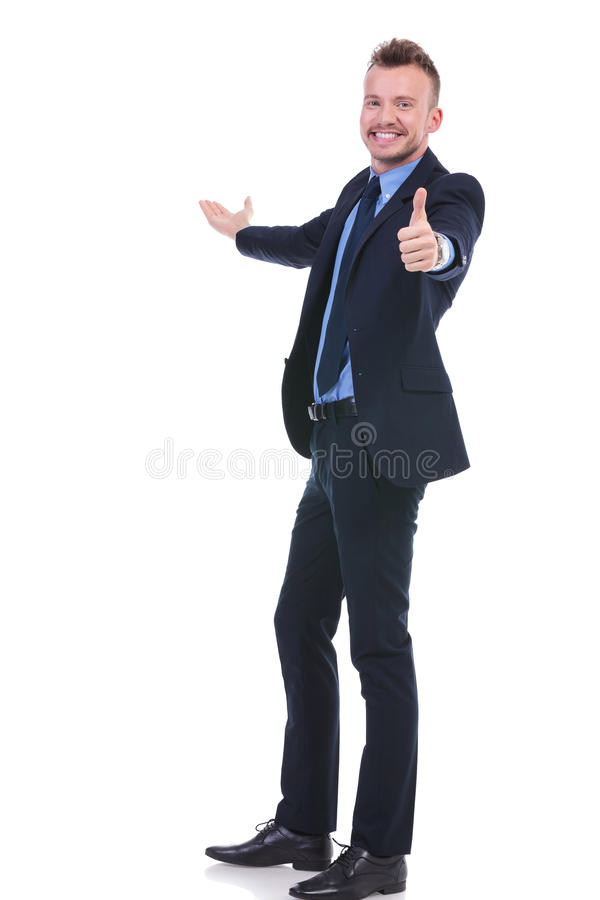 Business man presents something and shows ok. Full length picture of a young business man presenting something in the back while showing the thumb up gesture to stock photography