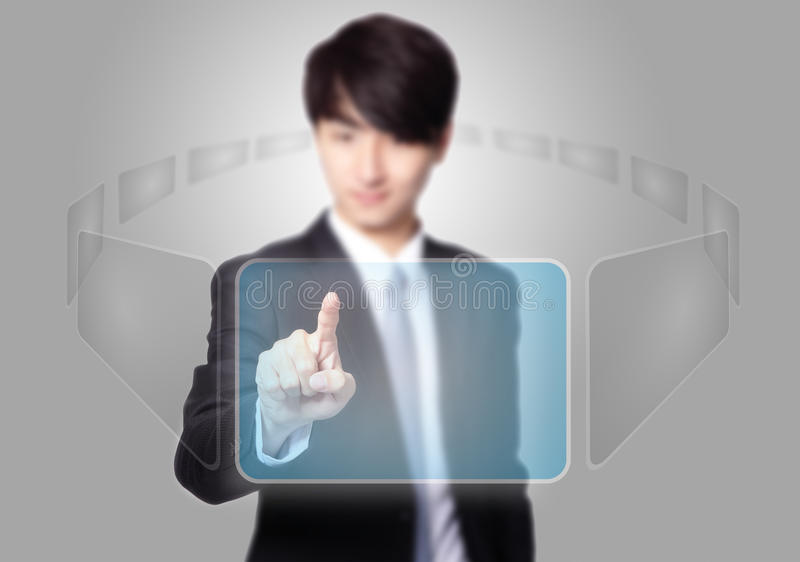 Business man pressing a touch screen button. With empty copy space on gray background, asian model stock photography