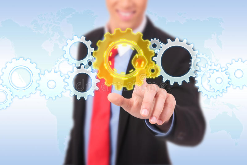 Business man pushing a cog button. On a word map background royalty free stock photos