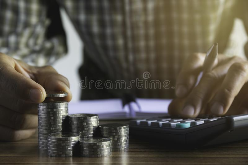 Business man putting  a coin on coins stack saving bank and account for his money all in finance accounting concept stock photos