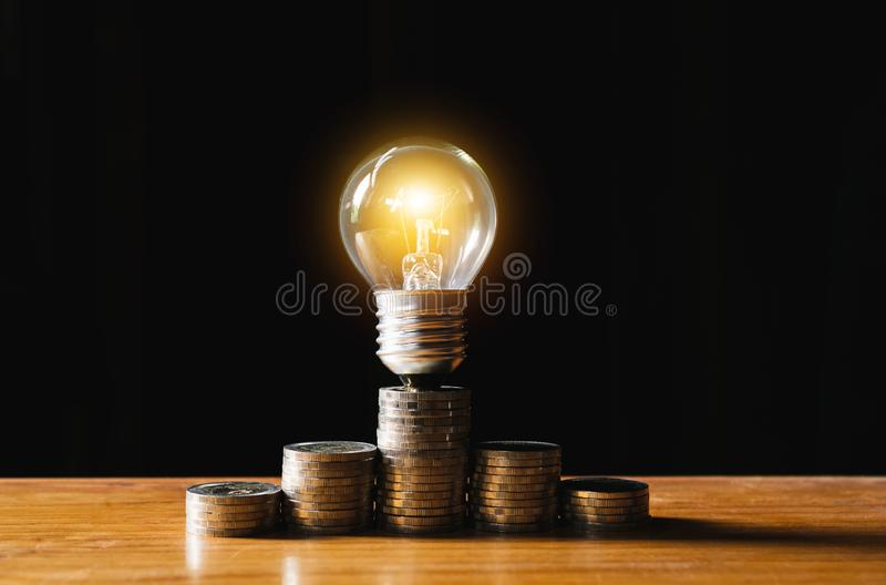 Coins and light bulb put on the wooden for saving money,energy concept in dark background. stock photo
