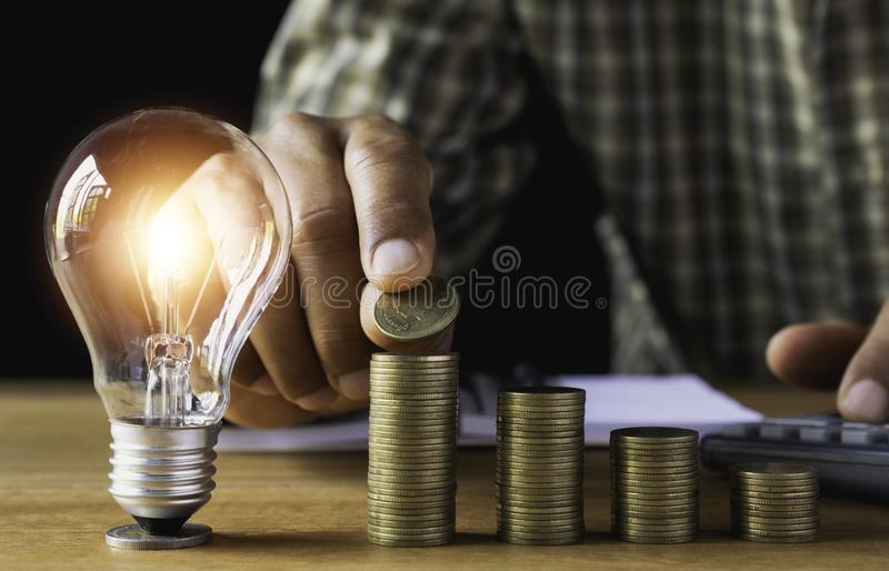 Business man putting coin with light bulb on table for saving bank and account for his money all in finance accounting concept royalty free stock image