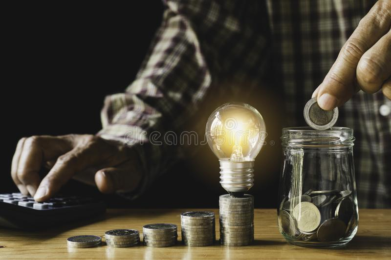 Business man putting coin with light bulb on table for saving bank and account for his money all in finance accounting concept stock photo