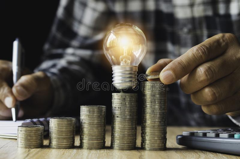 Business man putting a coin on coins stack saving bank and account for his money all in finance accounting concept royalty free stock photography