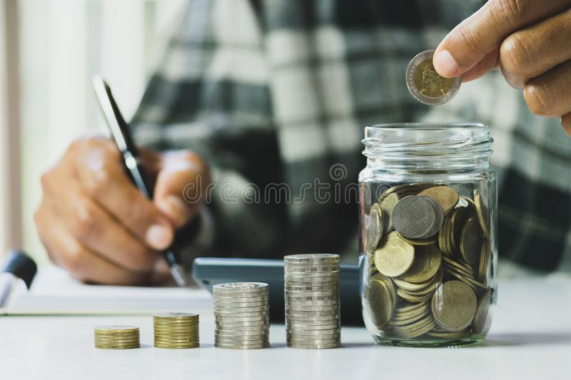 Business man putting the money in glass jar to saving,financial,accounting concept stock image