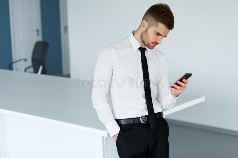 Man On Cell Phone : Business man reading something on the screen of his cell