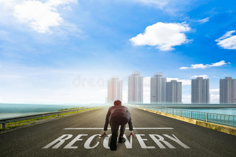 Business man ready to run toward the city on Recovery. stock photography