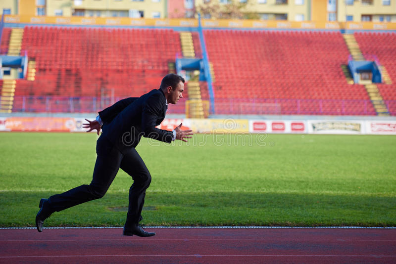 Business man ready to sprint. Business man in start position ready to run and sprint on athletics racing track royalty free stock images