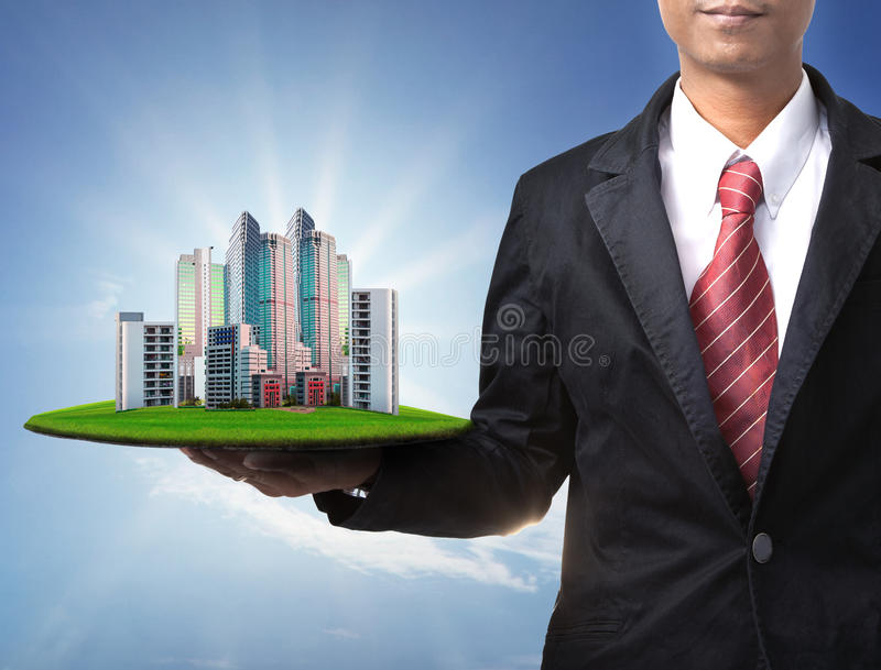 Business man and real estate in hand. Use for property land management and building construction theme stock photography