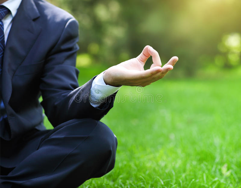 Business man relax in a park in the lotus position. Business man relaxing in a park in the lotus position. Close up royalty free stock images