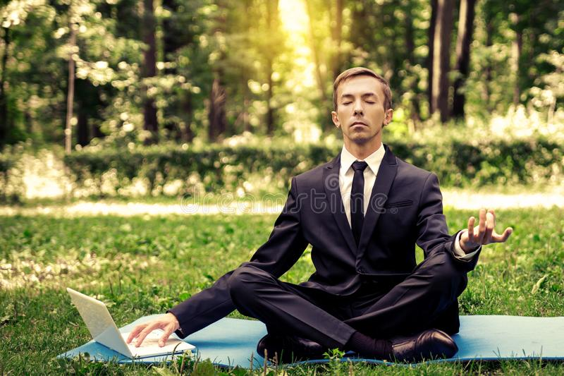 Business man relaxing in a park in the lotus position, he can`t relax in any way, typing text on a computer. With one hand royalty free stock photography