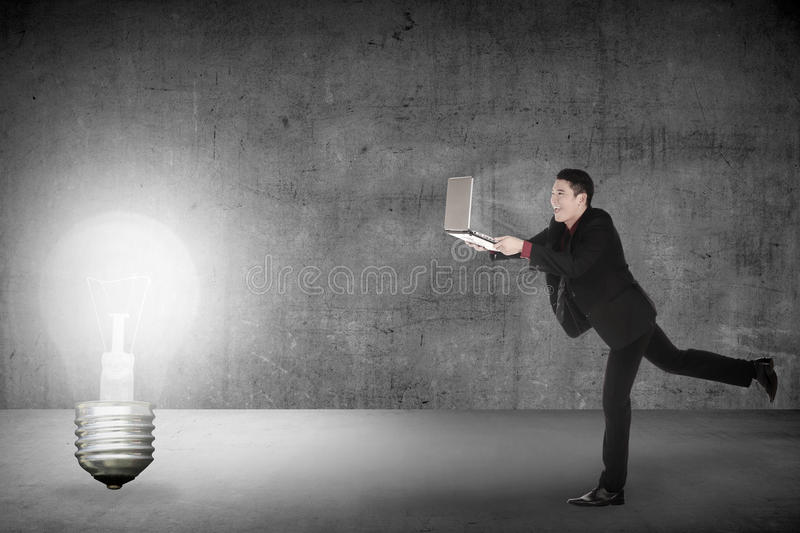 Business man run with laptop chasing light bulb. Making idea conceptual vector illustration