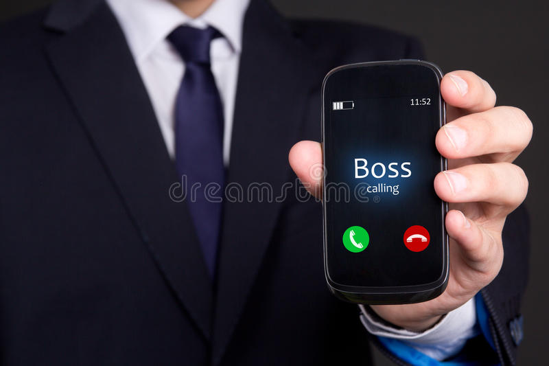 Business man's hand holding smart phone with incoming boss call. Business man's hand holding modern smart phone with incoming boss call royalty free stock photography
