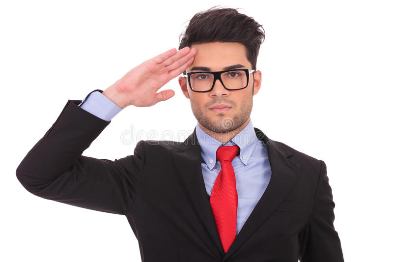 Business man saluting. Portrait of ayoung business man saluting and looking at the camera on white royalty free stock image