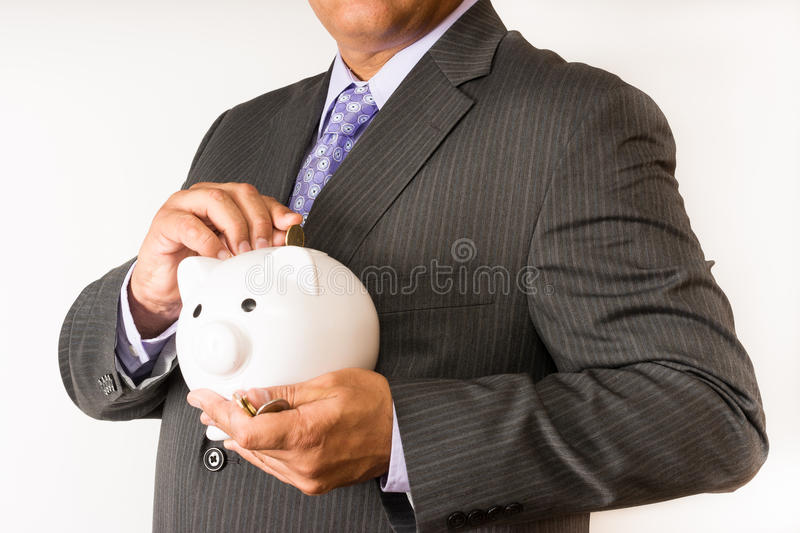 Business man saving some money. Man in a suit putting some change away in a piggybank. stock photography