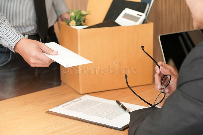 Business man sending resignation letter to boss and Holding Stuff Resign Depress or carrying cardboard box by desk in office. royalty free stock photography