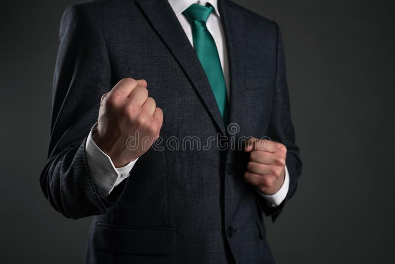 Business man. Business man is shaking a fists on a gray background. Business acumen or business protection. Leadership. Defending point of view abstact royalty free stock images