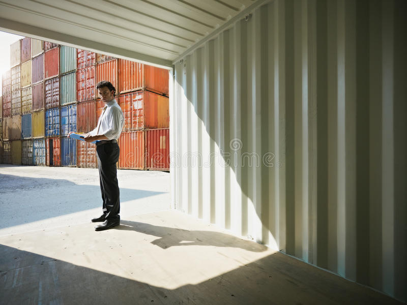 Business man with shipping containers stock photography