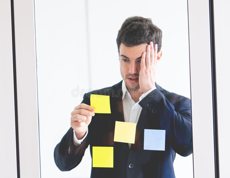 Business man shocking on idea on post it windows for plan. Business man is shocking on idea on post it windows for plan stock photo
