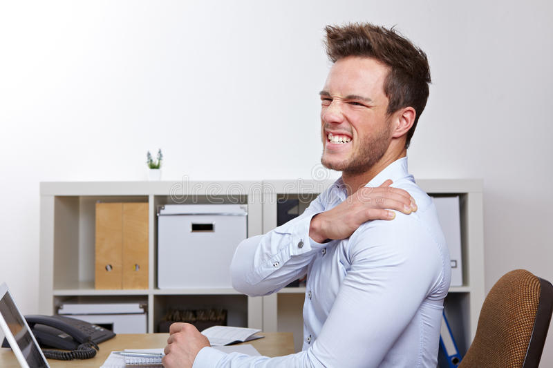 Business man with shoulder pain. In office at desk royalty free stock photos