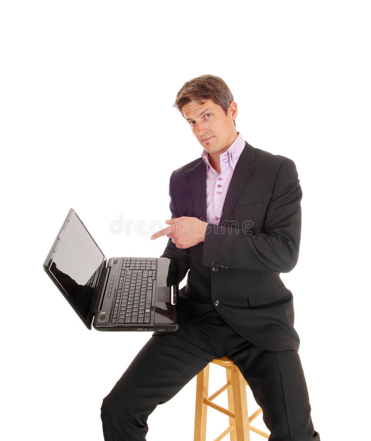 Business man showing on laptop. A business man in a gray suit sitting on a chair and pointing to his laptop screen, isolated for white background royalty free stock photography