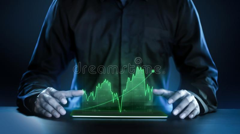 Business man showing profitable stock market holographic technology graphs in modern work background for the future. Company stock photography