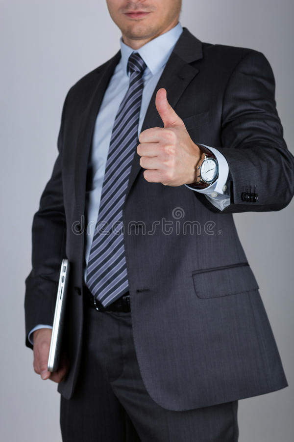 Business man showing thumbs up. Business man holding laptop and showing thumbs up over gray background. Business success concept royalty free stock images