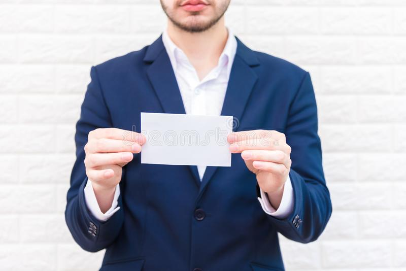 Business man showing white paper. Man  wearing blue suit and holding white blank card. Lifestyle and working concept. Business and stock photo