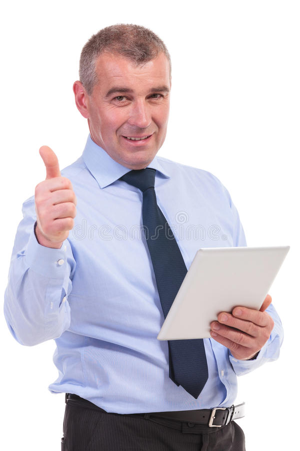 Business man shows thumb up with tablet in hand. Business man showing the thumb up sign to the camera while holding his tablet. on a white background royalty free stock images