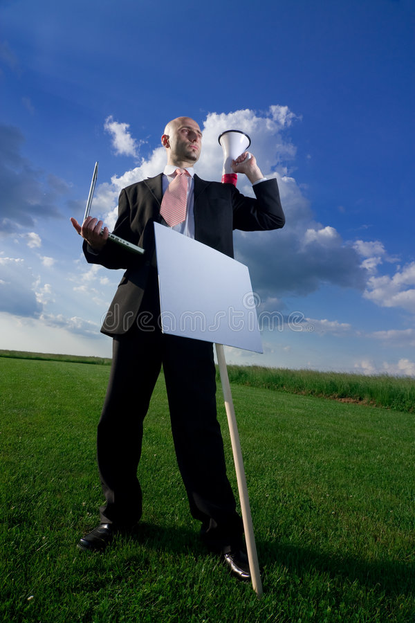 Business Man with a Sign. A business man holding a laptop computer and a bullhorn in front of a blank sign stock photography