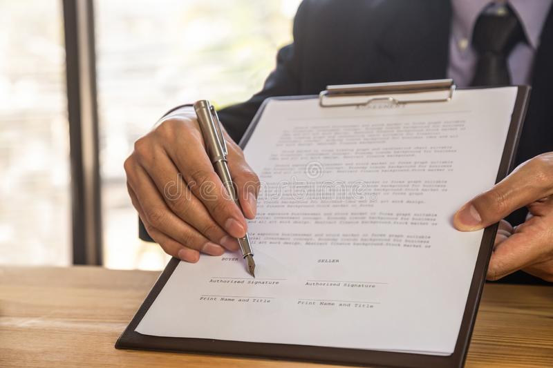 Business man signing a contract. Owns the business sign personally, director of the company, solicitor. Real estate agent holding stock image
