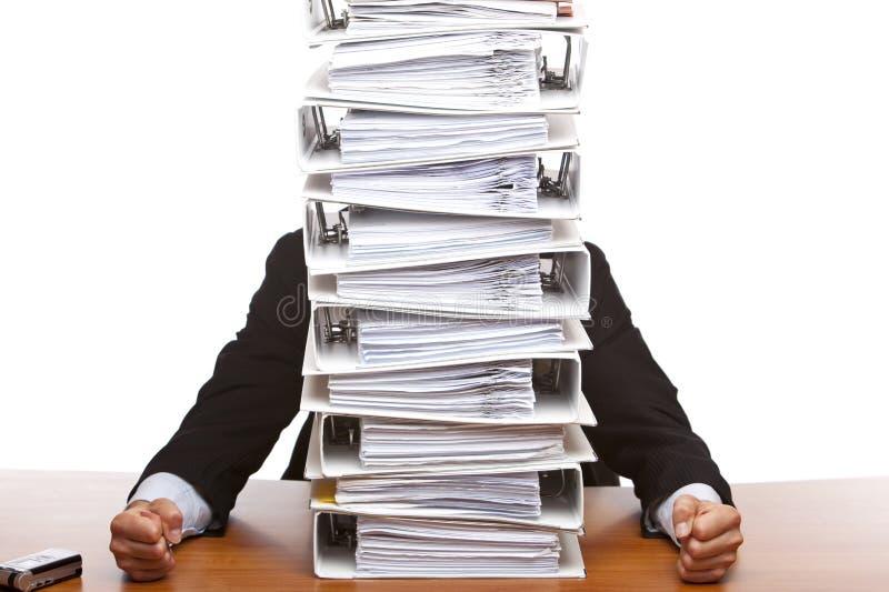 Business man sits beside paperwork folders stock image